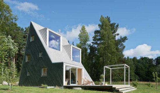 Arquiteto projeta casa de veraneio feita com madeira reaproveitada para sua família